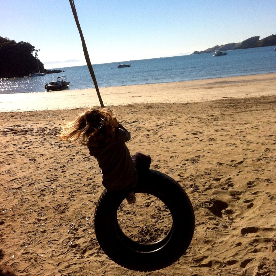 Child on rope swing Waiheke Island